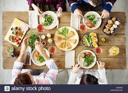 dinner table top view. top view of four people eating at festive dinner table with delicious food in cafe or