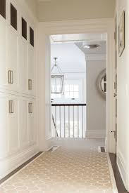 elegant hallway with built in white linen closets accented with nickel hardware over dark hardwood floors layered with a custom beige and ivory geometric