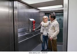people standing in elevator. beautiful senior couple with luggage standing in modern elevator. people travelling. - stock image elevator e