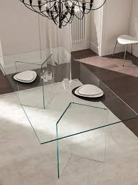 ultra-minimalist dining table with geo glass legs and a glass tabletop, the  dishes