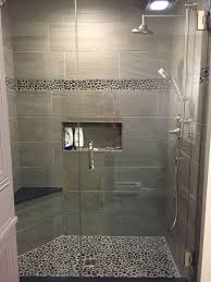 Large charcoal black pebble tile border shower accent.  https://www.pebbletileshop.com/gallery/Charcoal-Black-Pebble-Tile-Border- Shower-Accent.html#