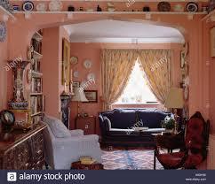 Blaues Sofa Vor Fenster Mit Gemusterten Cremefarbene Vorhänge In