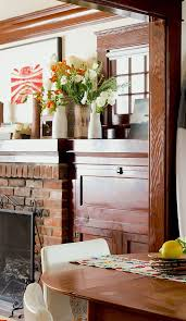 mia maestro craftsman home with a brick fireplace and wood stained trim and fireplace surround