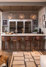 Three Arteriors Beck Pendants illuminating a marble waterfall bar fitted  with a wet bar sink and
