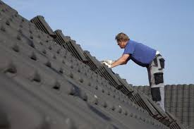 a roofer shingling a house