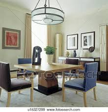 cylindrical light above sculpture on light wood table in modern dining room with upholstered blue and brown chairs