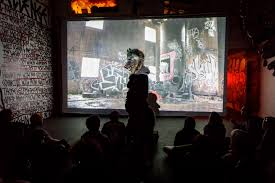 wolfs stands in the midst of the crowd during a screening of wastedland 2 all photos by the author for hyperallergic