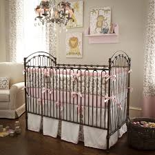 dark brown steel crib with bars on the side board combined with pink gray fabric bedding set