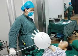 surgeon nurse chinese woman makes a balloon out of a surgery glove to comfort