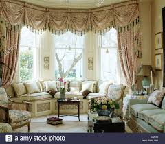 Silk Curtains For Living Room Swagged And Tailed Cream Curtains In Living Room With Mauve Sofa