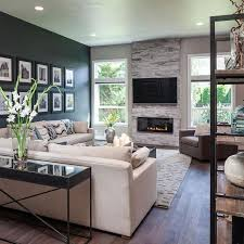 the dark accent wall fireplace and custom wood floors add warmth to this open
