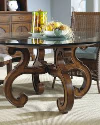 small glass top dining table furniture round with brown wooden carving base on beige rug elegant