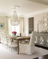 beautiful dining room features a french dining table lined with white cane back dining chairs with skirted seat cushions as well as slipper captain dining