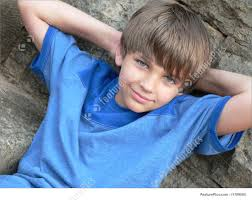 cute boy in blue t shirt lying on back with arms behind head he