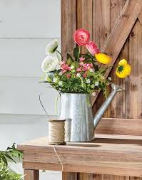 product category fl metal watering can with faux flowers sitting on a wood workbench