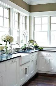 black countertops with white cabinets absolute black in a kitchen with a farmhouse sink and white shaker cabinets black tile backsplash white cabinets