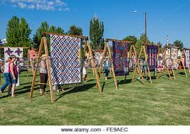 QUilts on display at the Sisters Outdoor Quilt Show, SIsters ... & ... Oregon · Tourists look at quilts displayed on A frame racks at the  Sisters Outdoor Quilt Show, Adamdwight.com