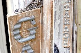 aged wood plank with corrugated metal letters that make up this garage sign