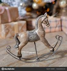 small wooden rocking horse under the tree with gifts stock photo