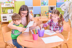 Female teacher working with two students in a classrom