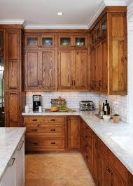 Crown molding around cabinets is painted white to match the ceiling, not natural  wood to