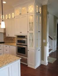 kitchen cabinets with glass doors on top tall white narrow lit light counters hardwood flooring tan