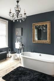 black bathroom gold mirror and delicate chandelier in dark over tub