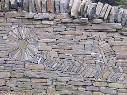 using alternating layers of slate to create the petals and detail in the leaf  on stone wall artwork with the art of the dry stack stone wall insteading
