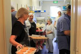 busy kitchen. People With Hairnets And Aprons In A Small Busy Kitchen