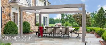 aluminum shade structure with fabric canopy over stone patio next to traditional stone house aluminum fiberglass pergola kits