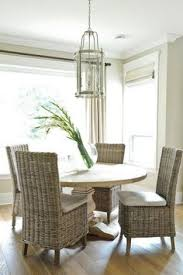 cool round salvaged wood dining table with wicker dining chairs transitional dining room