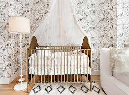 a two tone french crib sits on a black and white moroccan rug beneath a sheer canopy hung in front of a wall covered in kalahari vignettes wallpaper lit by