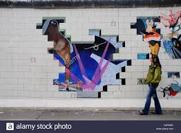 a girl walks past the album artwork of pink floyd the wall painted on the berlin wall at the east side gallery on pink floyd the wall cover artist with a girl walks past the album artwork of pink floyd the wall painted