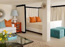 adorably stylish studio apartment with nice wall decor colored beautiful furniture and seperated by curtain