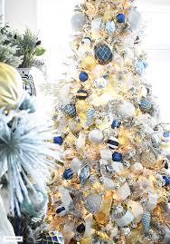 Beautiful, flocked Christmas tree adorned with navy, light blue and elegant  metallics, ...