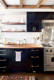 Dark kitchen cabinets with open shelves and brass hardware. (Black cabinets  and butcher block counter tops.