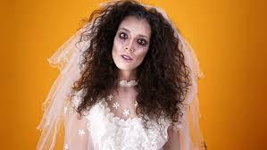 crazy dead bride on wearing wedding dresakeup looking at the camera over orange background