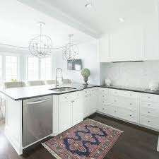 sphere chandeliers over black and white kitchen peninsula