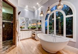 master bath with tub and pendant lights with hanging glass