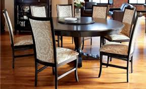 60 inch expandable round pedestal dining table with wooden base painted with black color for large living room with 7 wooden chairs with fabric cover and
