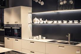 white kitchen cabinets floating shelves with led strip lighting and gray background