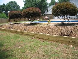 eliminate steep difficult to mow slopes stop erosion and create attractive planting beds with an easy to assemble wood retaining wall