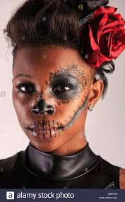 a young woman with face paint in the form of a sugar skull decorated for dia de los muertos