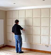 a man putting up padded wall tiles