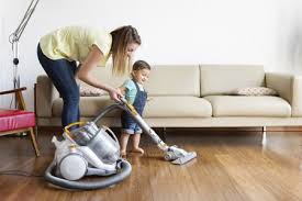 woman and young boy wearing denim dungarees standing in front of sofa hoovering hardwood