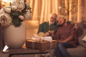 close up vase with beautiful flowers and gift locating on table happy senior couple hugging