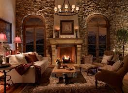 living room round rustic chandelier over white sofa and 2 brown fabric accent chairs also rectangular industrial coffee table front of stone fireplace