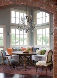 banquette breakfast nook dining room traditional with round dining table brick archway