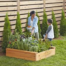 woman and small boy in front of vegetable garden