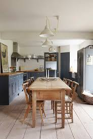 Grey kitchen with wooden table and pendant lights